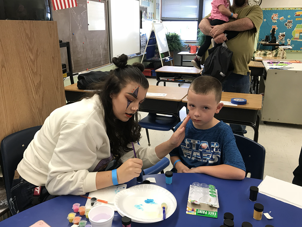 Michaela Tabor paints the face of an SES student.